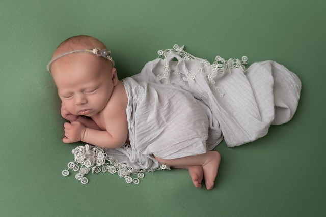 Newborn photographer in Milton Keynes captures image of baby girl on green