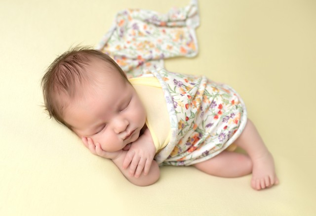 Newborn photographer in Milton Keynes captures image of baby girl with yellow blanket and flowers