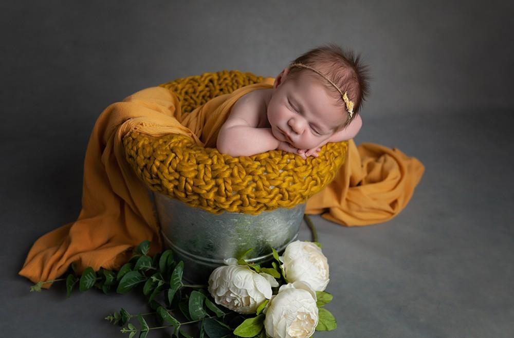 Newborn photographer in Milton Keynes captures image of baby girl in bucket with yellow blankets