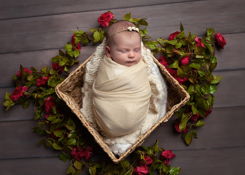 Newborn photographer in Milton Keynes captures image of baby girl surrounded by roses and leaves