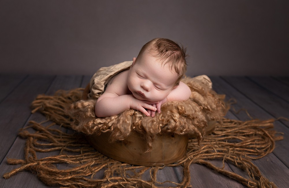 newborn baby boy in photoshoot with brown blankets