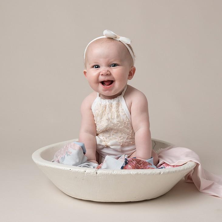 cute sitting baby girl by photographer in Milton Keynes