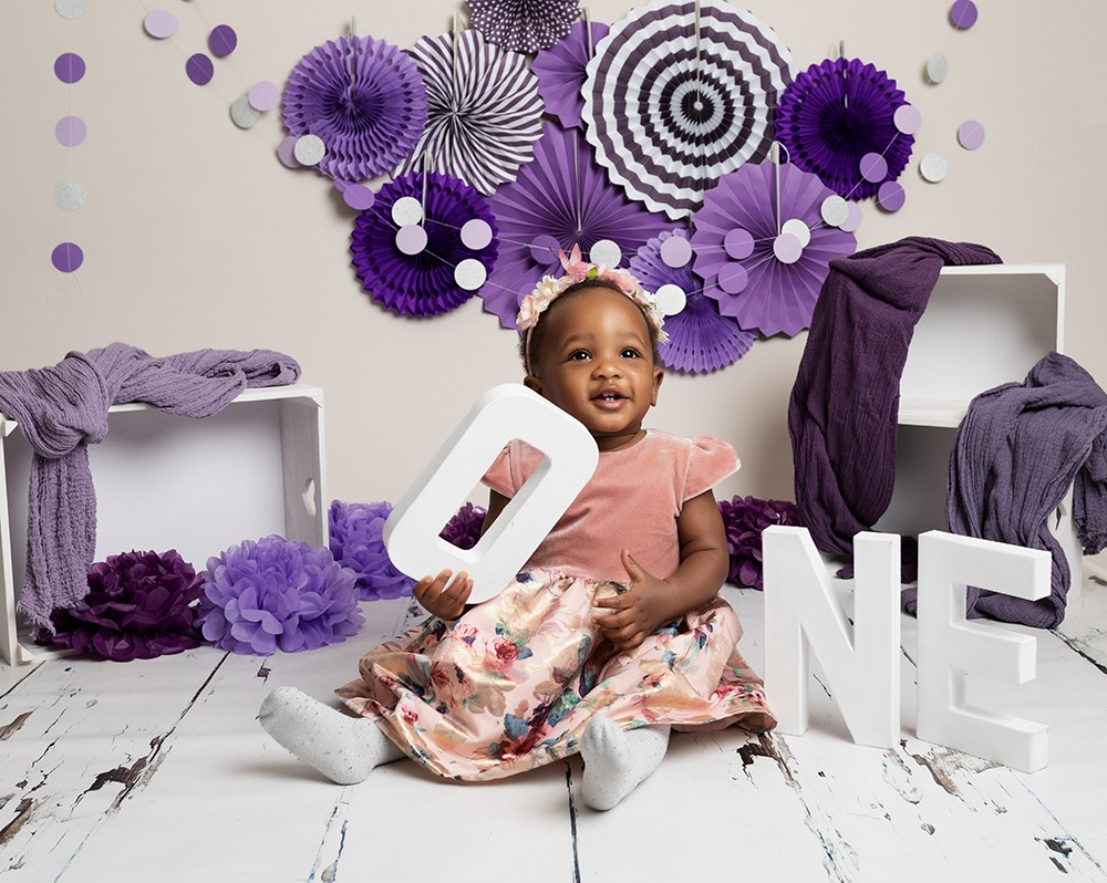 baby girl with purple decorations at cake smash photo shoot in milton keynes