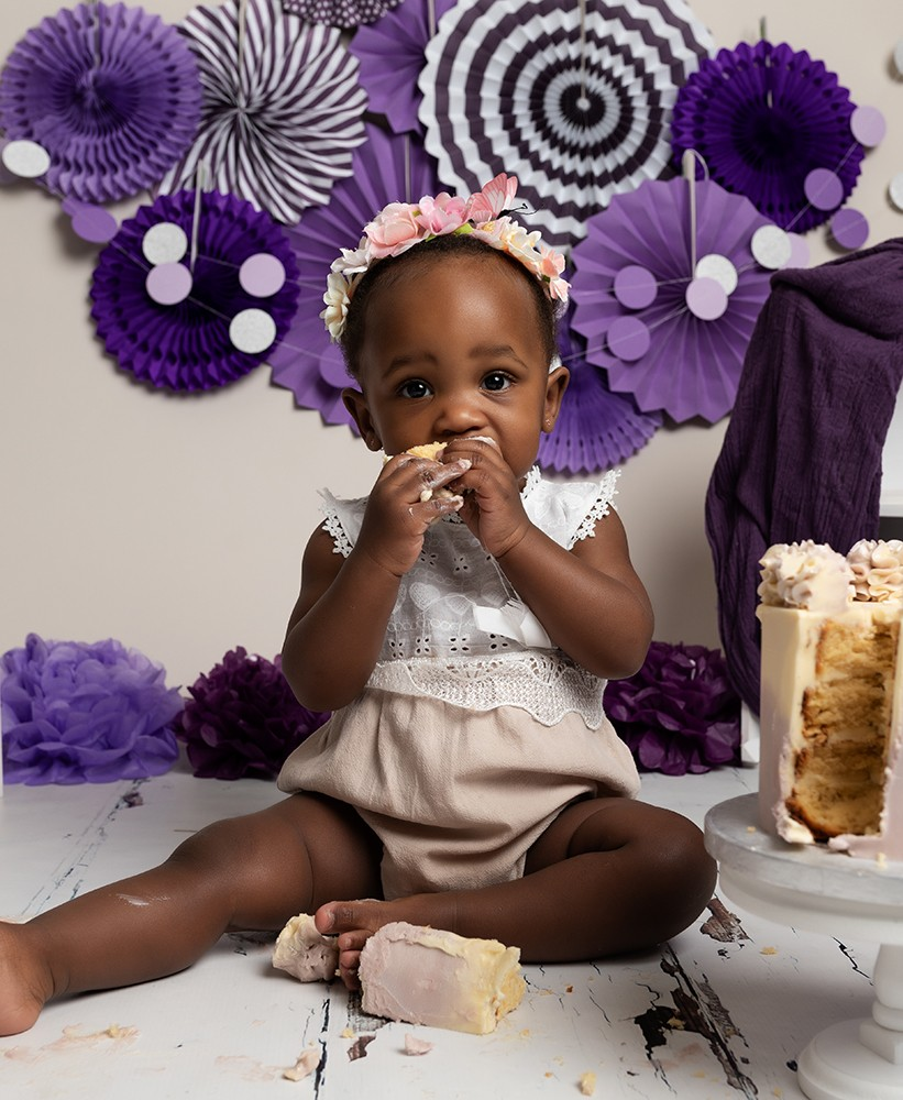 baby girl with purple decorations eating cake at cake smash in milton keynes