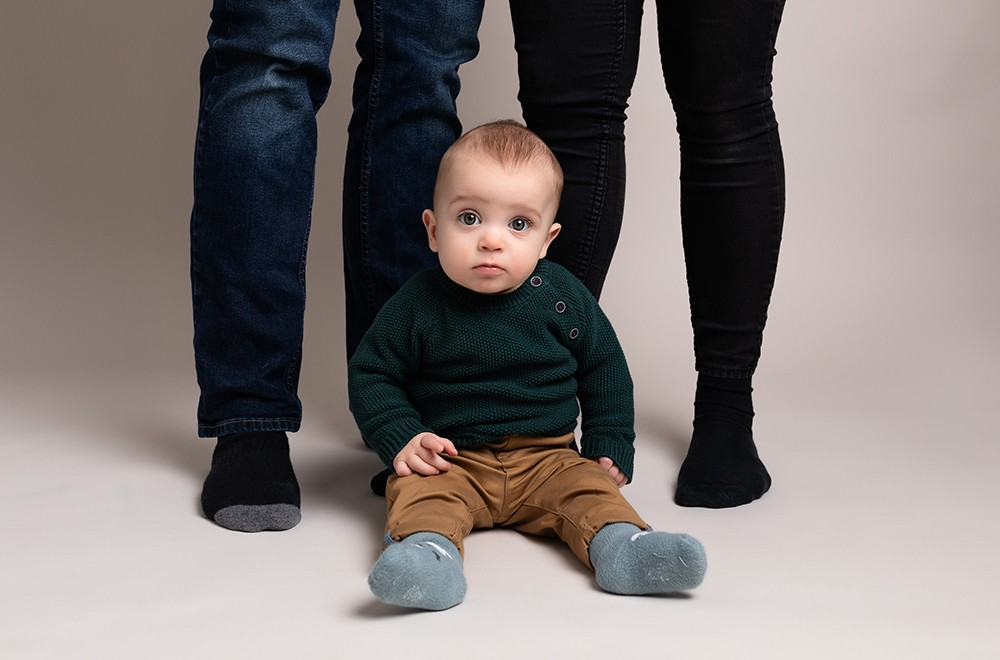 baby boy witting with parents by baby photographer in Bedford and Milton Keynes