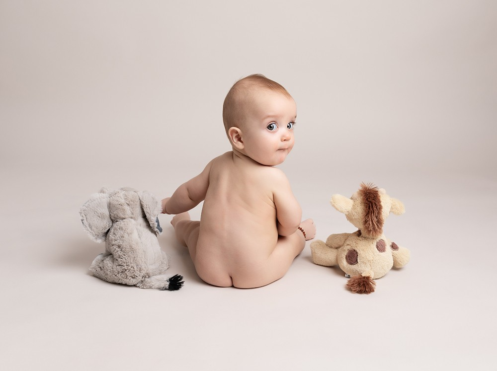 Sitting baby boy with toys by baby photographer in Bedford and Milton Keynes