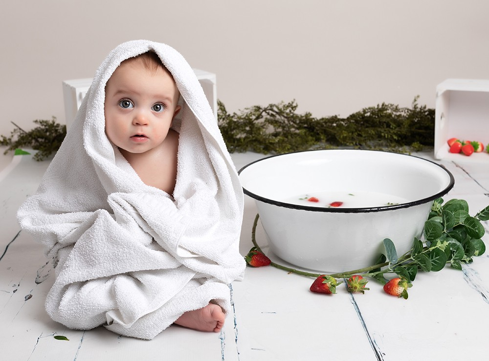 baby boy sitting wrapped in towel by baby photographer in Bedford and Milton Keynes