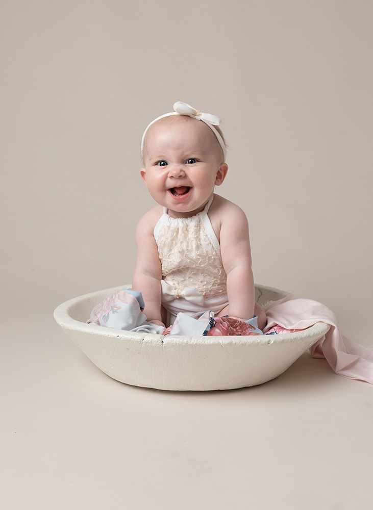 sitting baby girl with a big smile by baby photographer in Bedford and Milton Keynes