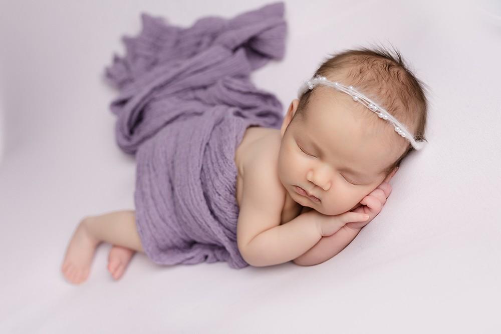 newborn baby girl sleeping on pastel pink by newborn photographer in Milton Keynes