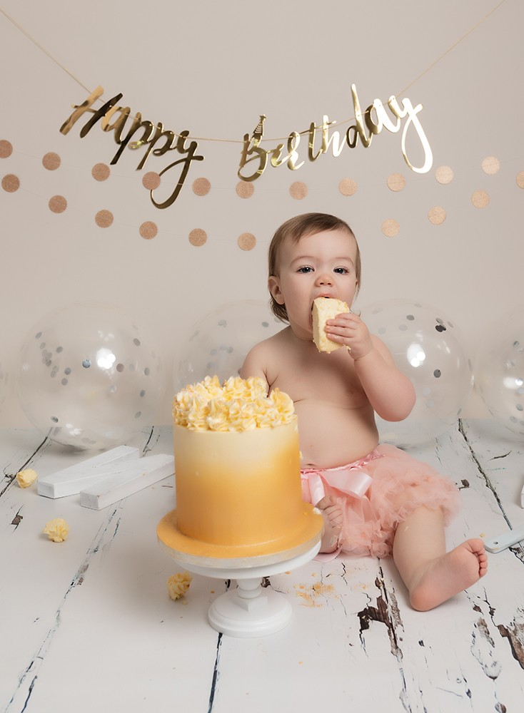baby girl with gold cake at first birthday cake smash photoshoot in milton keynes