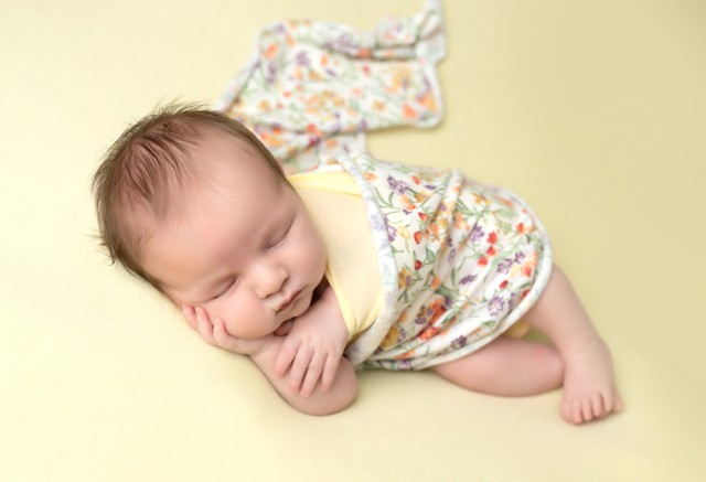Newborn Photographer in Milton Keynes baby girl with bright yellow baby photo from baby photoshoot