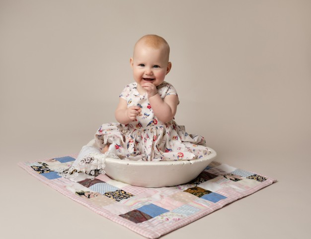 Baby Photographer Bedford baby girl 6 months on patchwork quilt