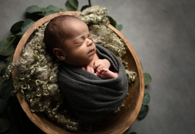 Newborn Photographer in Milton Keynes baby boy with soft green fabric baby photo from baby photoshoot