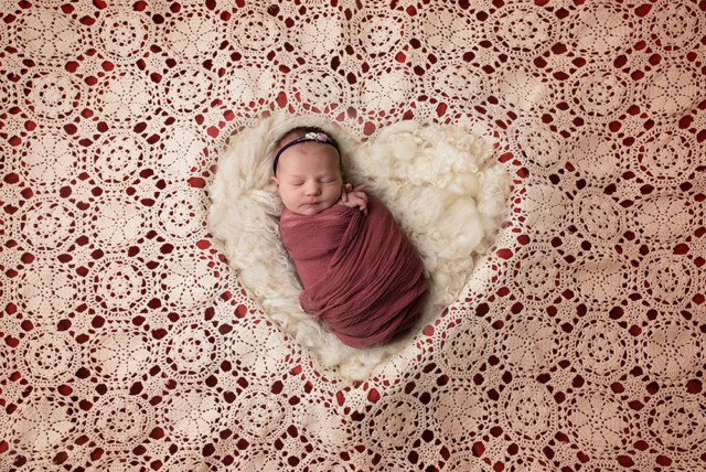 Newborn Photographer in Milton Keynes baby girl with red lace heart shape baby photo from baby photoshoot
