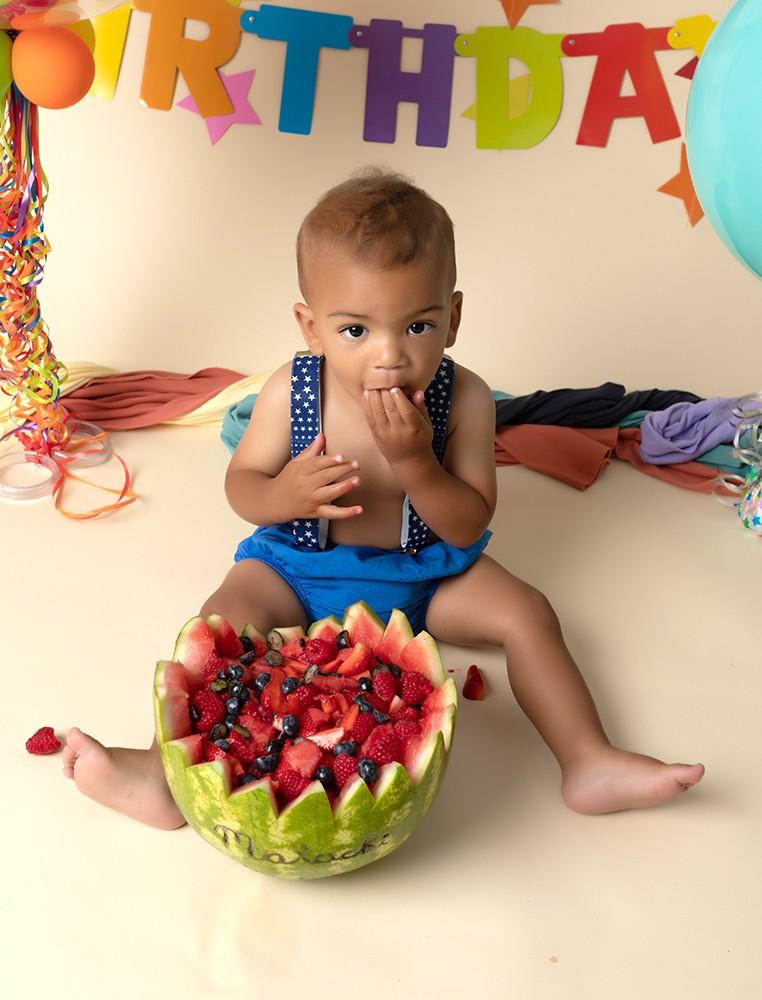 first birthday celebration with baby boy having fruit smash as an alternative to a cake smash