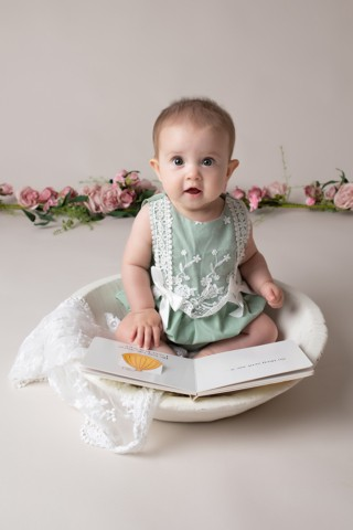 Baby Photographer Bedford baby girl 6 months in green with a book