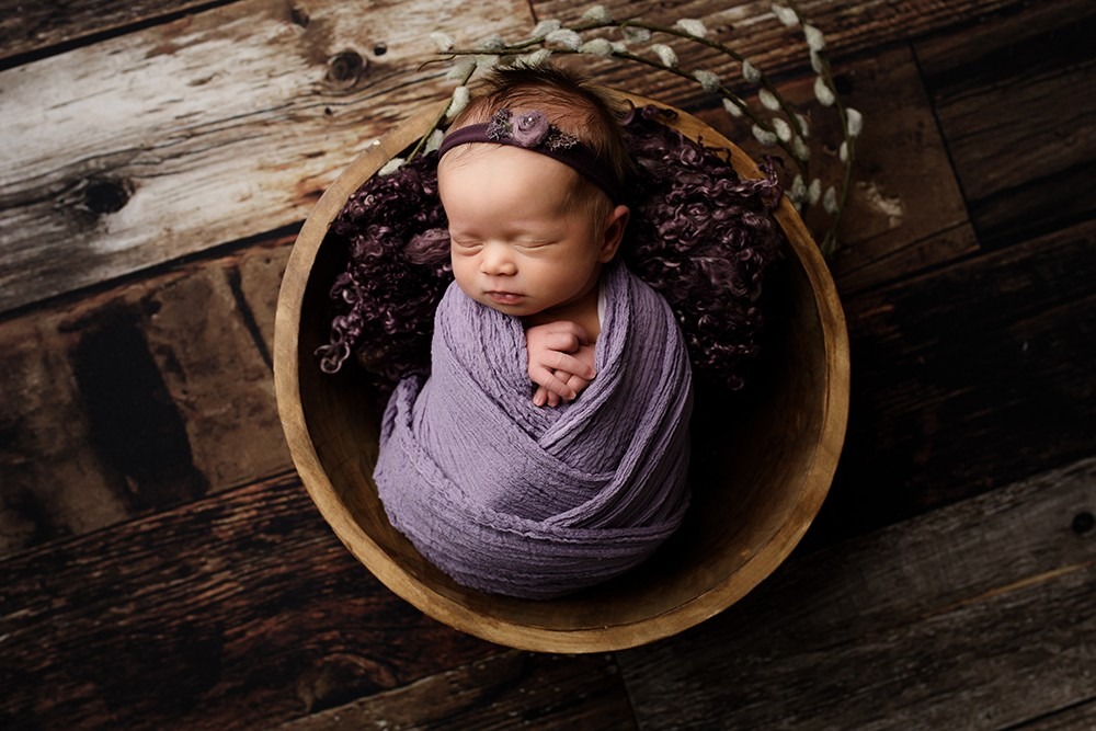 newborn baby girl in wooden bowl with natural styling newborn photographer in northampton and milton keynes