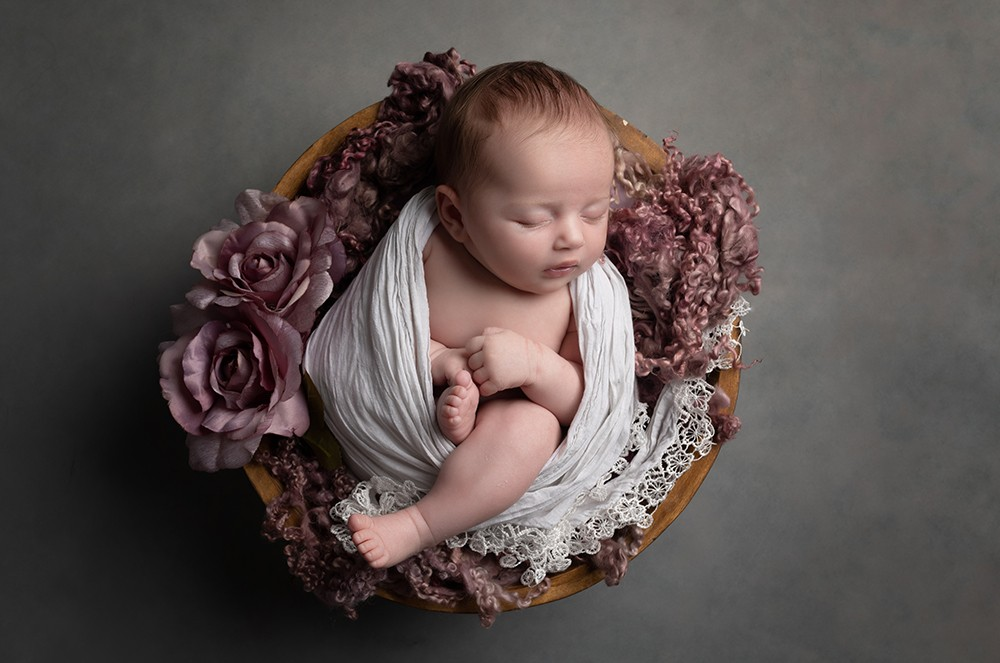 Newborn Photographer in Milton Keynes baby girl with pink fabric and grey baby photo from baby photoshoot