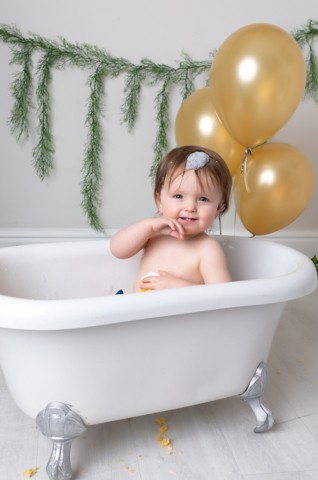 Cake Smash Milton Keynes baby baby girl in a bath after first birthday cake smash