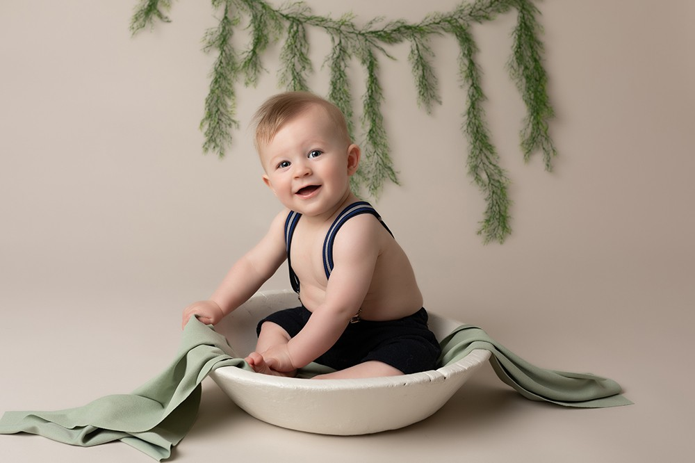 Baby Photographer Bedford baby boy in a bowl with green decorations