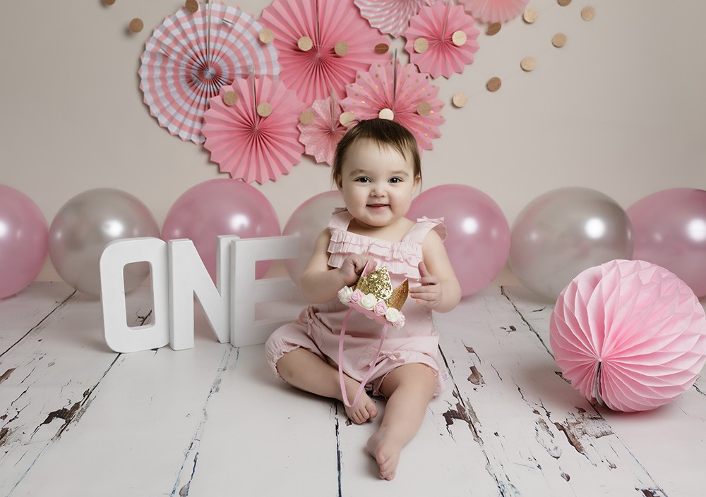 baby girl with pink decorations at first birthday photoshoot in milton keynes