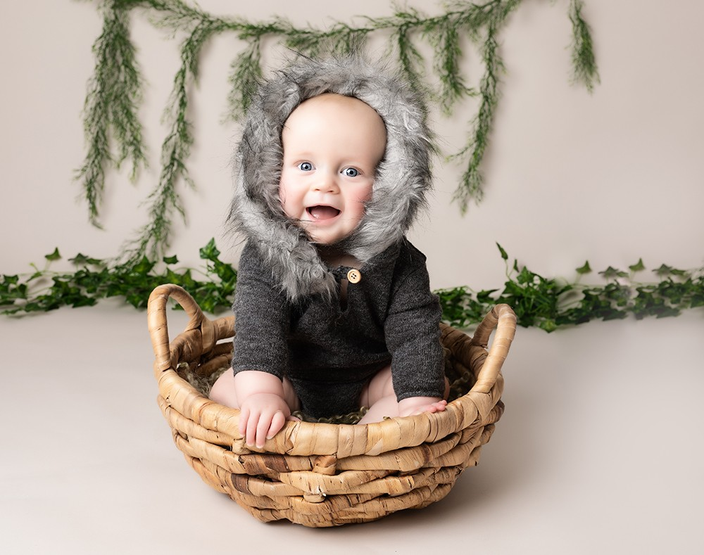 older Baby boy in a basket 6 months big smile by baby photographer in Bedford and Milton Keynes