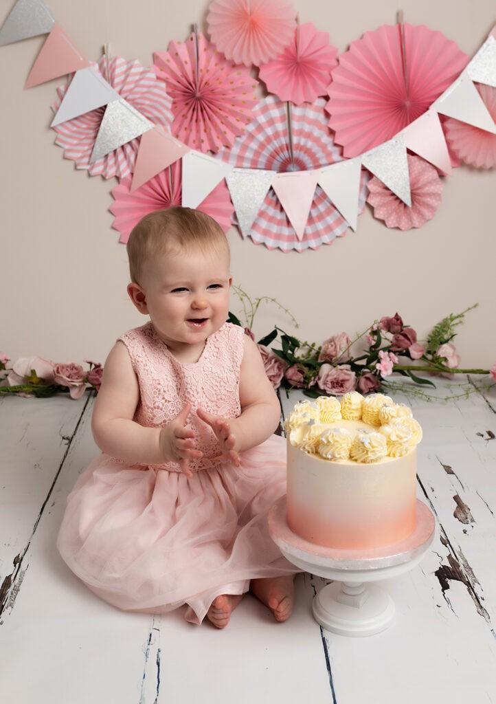 baby girl eating pink cake for birthday photoshoot in Milton keynes