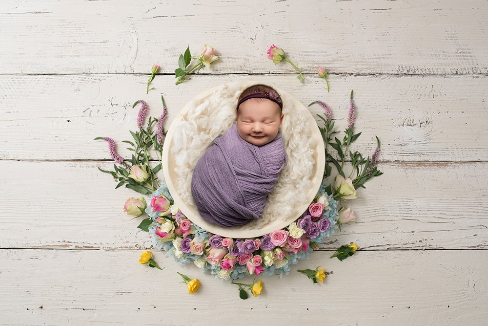 baby girl with big smile in a cream bowl with spring flowers by newborn photographer in milton keynes and northampton