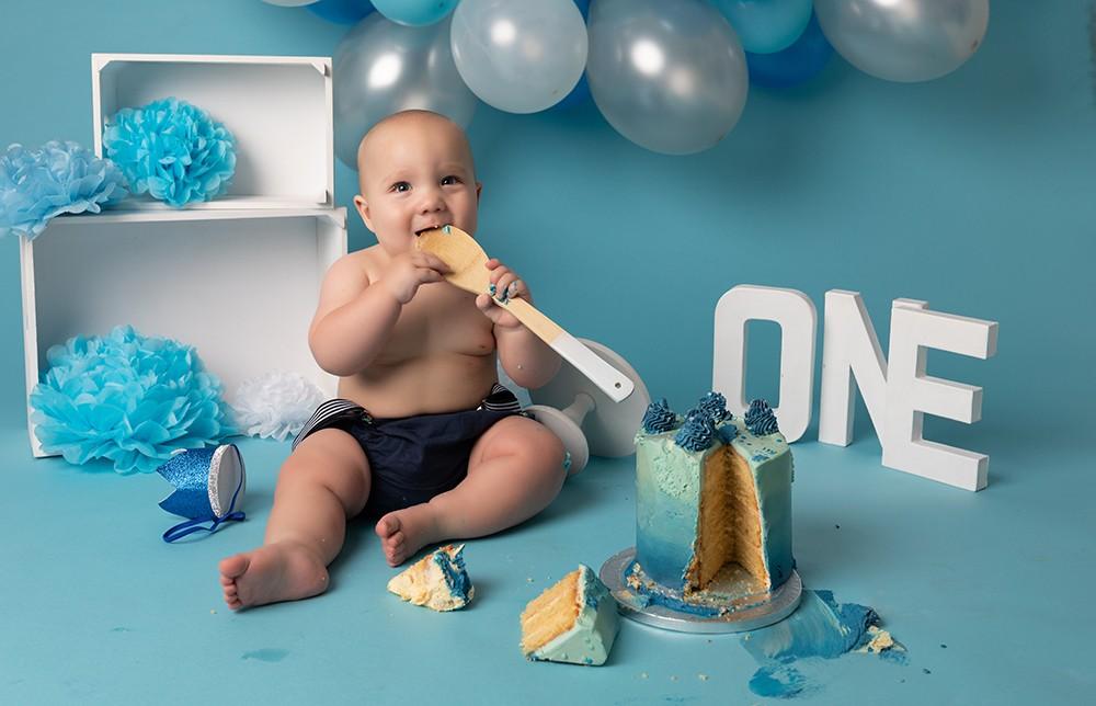 Cake Smash Milton Keynes baby boy eating cake at first birthday photoshoot near Northampton