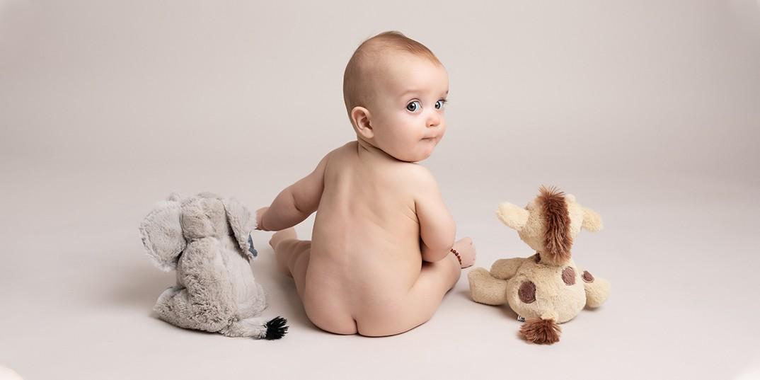 baby boy 6 months sitting with teddies