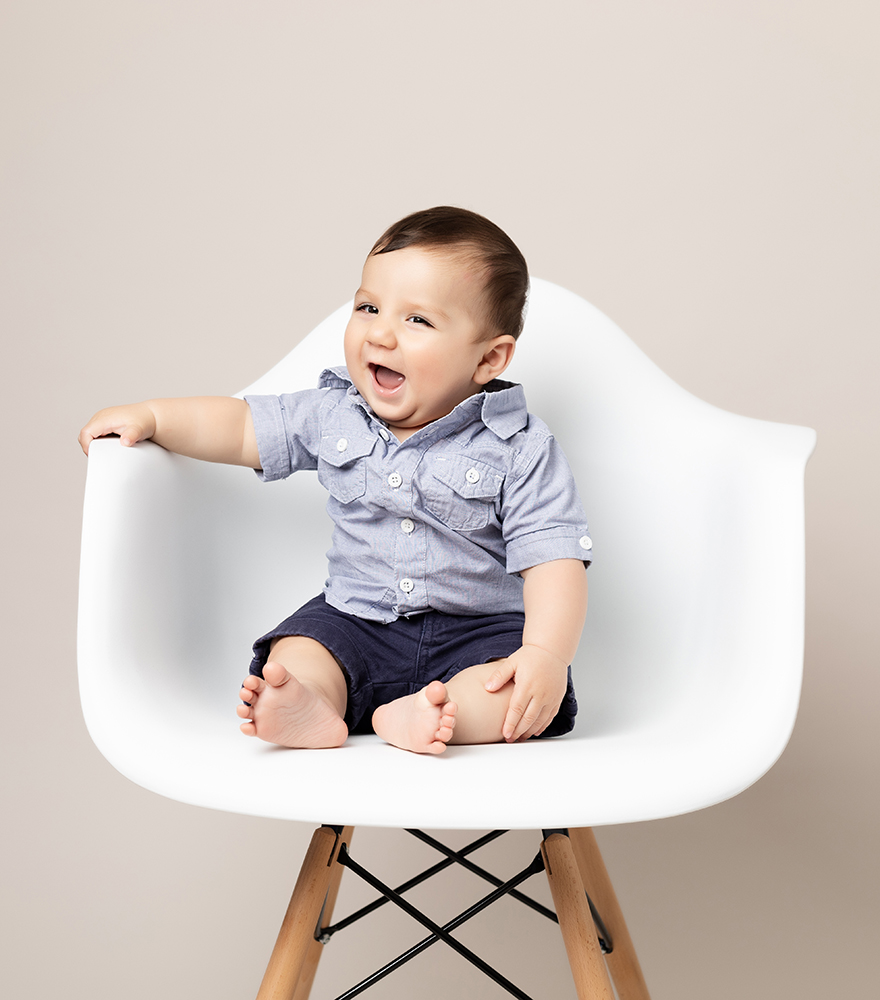 baby boy smiling in chair by Baby Photographer Bedford