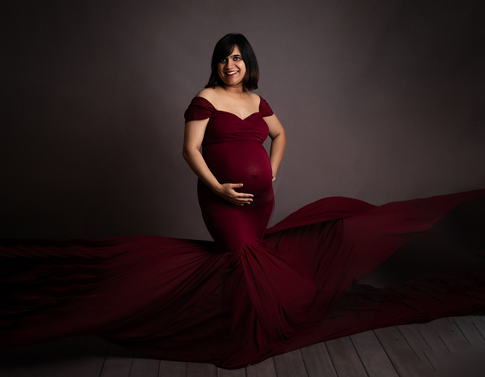 expectant mama in flowing red dress by pregnancy photographer