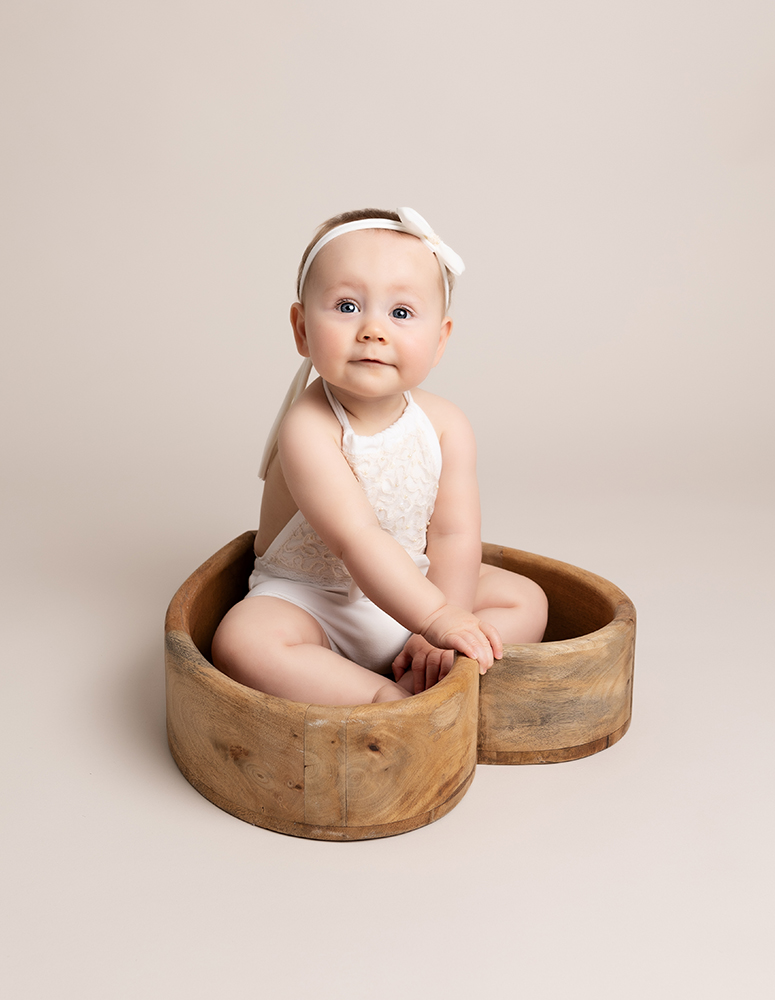 baby girl in heart shaped bowl on neutral background by Baby Photographer Bedford