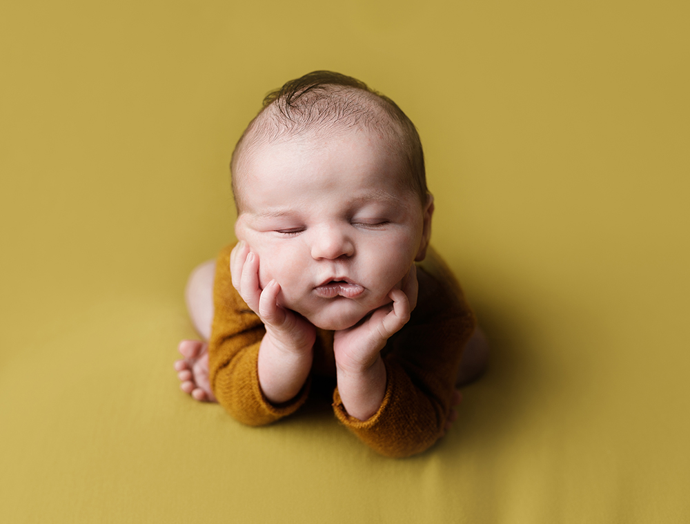 baby boy on yellow blanket froggy pose by Newborn Photographer in Milton Keynes and Northampton