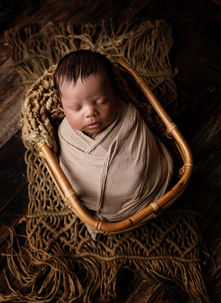 baby boy in a basket newborn photoshoot natural colours by newborn photographer in northampton and milton keynes