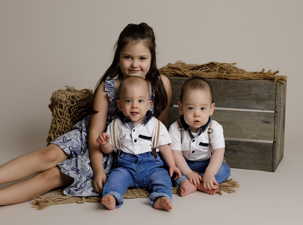 twin babies with older sister by Baby Photographer Bedford