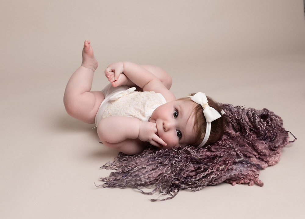baby girl sucking fingers on pink rug by Baby Photographer Bedford