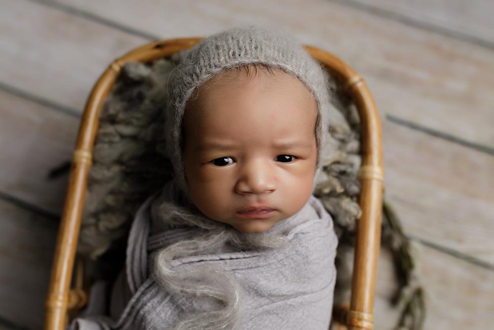 baby boy in grey hat by newborn photographer in northampton and milton keynes