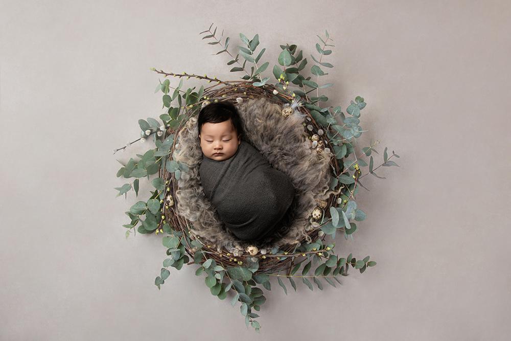 baby boy in leafy basket by newborn photographer in northampton and milton keynes