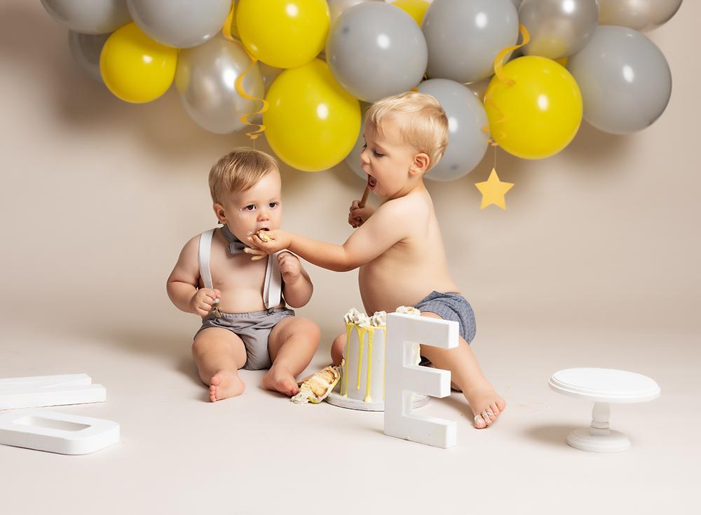 1 year old boy eating cake with big brother at Cake Smash Milton Keynes