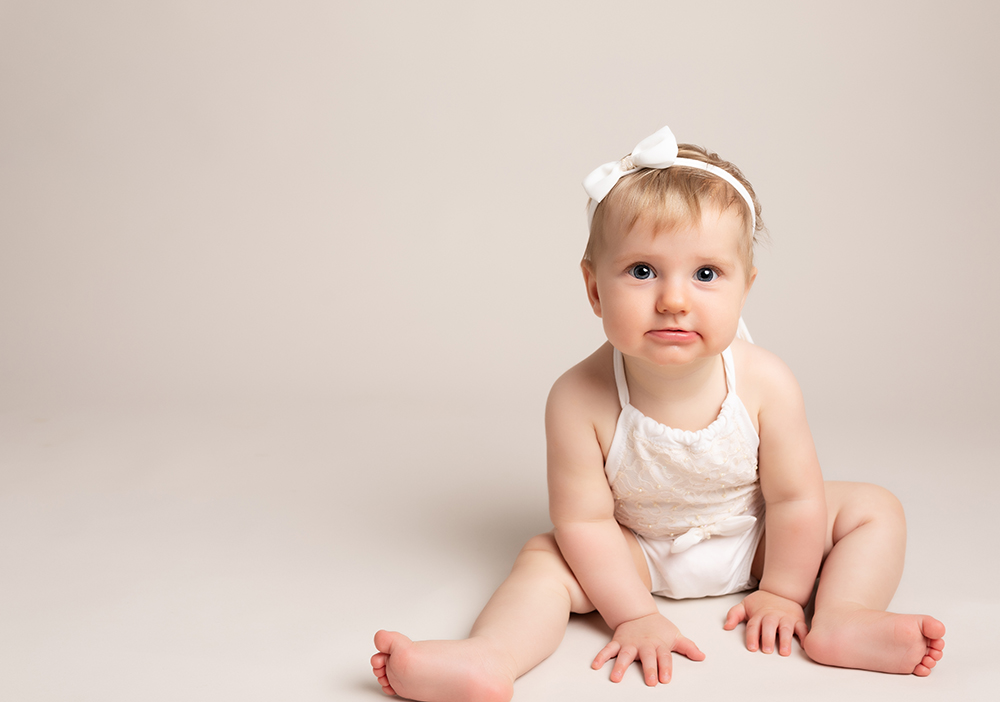 baby girl in white romper by Baby Photographer Bedford