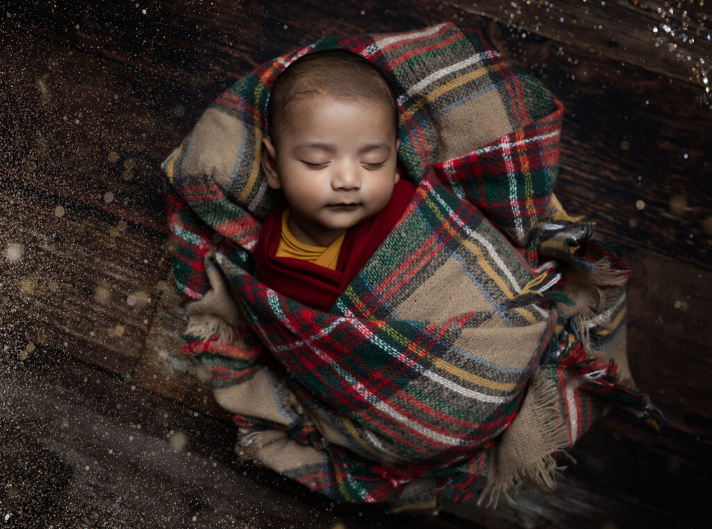 Sleeping baby boy with a tartan blanket at Older newborn photoshoot Milton Keynes