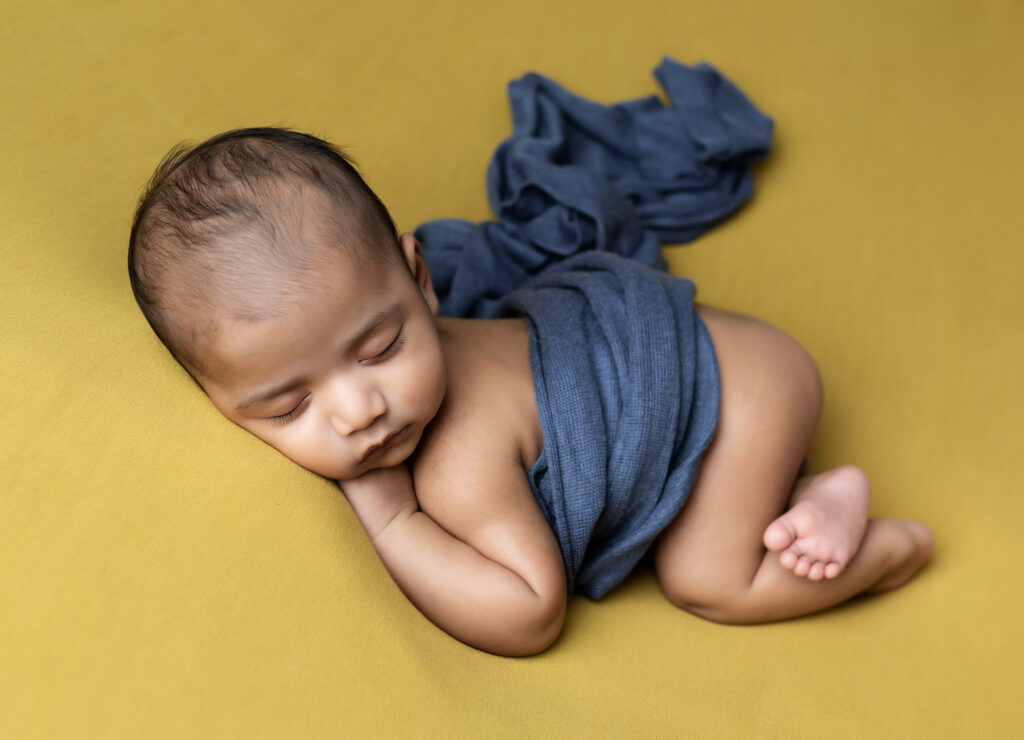 Sleeping baby on yellow and blue at Older newborn photoshoot Milton Keynes