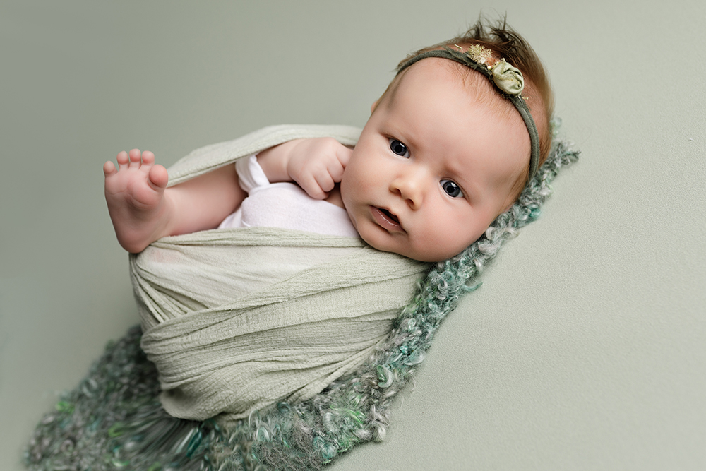 baby girl on green blanket at Older newborn photoshoot Milton Keynes